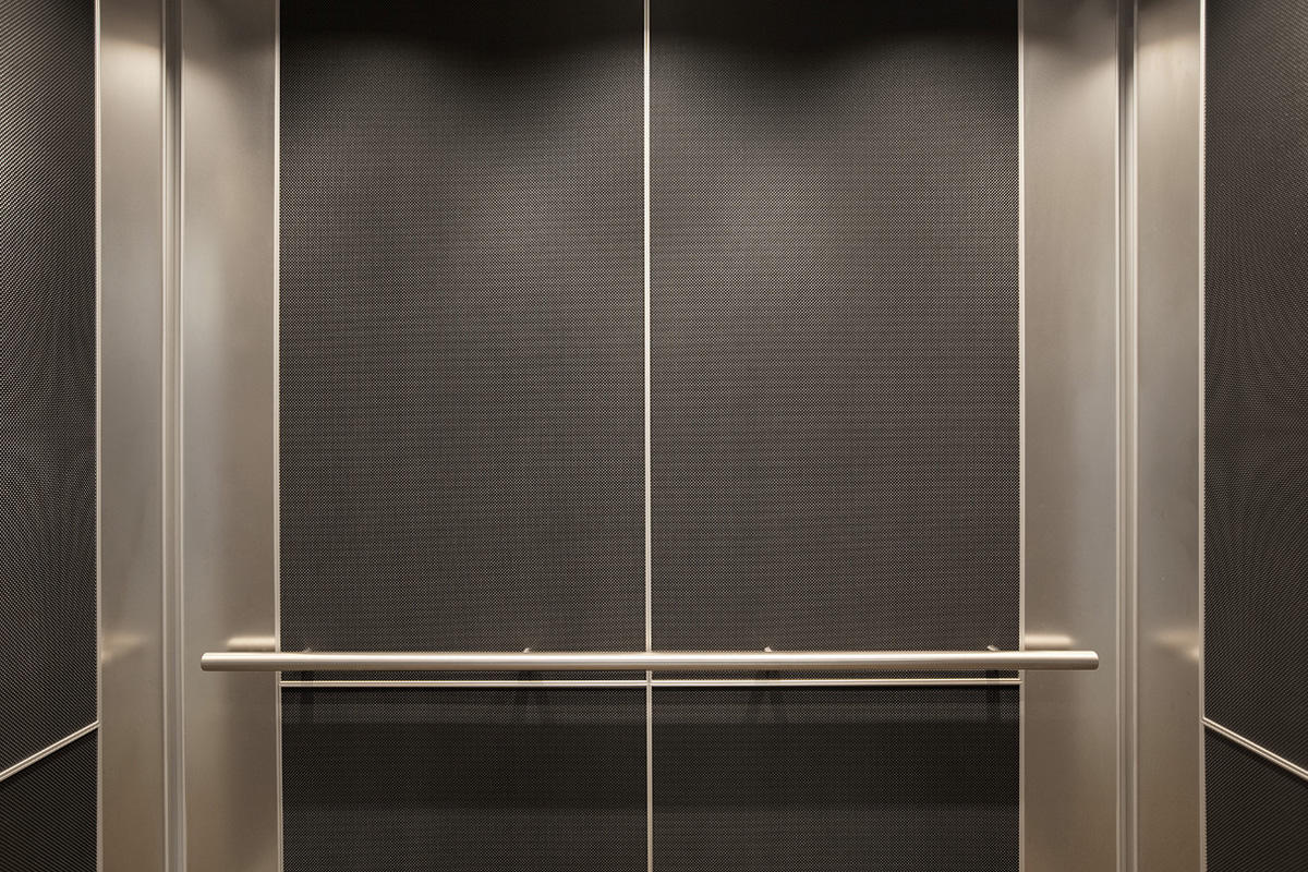 elevator interior door. levele-102 elevator interior with customized panel layout; capture panels in bonded aluminum dark patina and vancouver pattern, stainless steel door 2