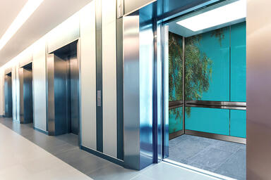 Elevator interior wall panels in ViviSpectra VEKTR glass with custom interlayer